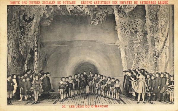 """Carte postale ancienne représentant une photo de la représentation """"Les jeux du dimanche"""": chorale d'enfants sur scène."""