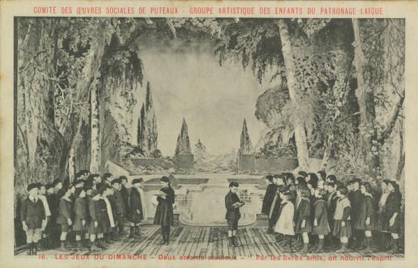 """Carte postale ancienne représentant une photo de la représentation """"Les jeux du dimanche"""": """"Deux enfants studieux - Par les livres amis, on nourrit l'esprit""""."""